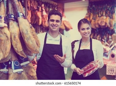 woman and  man selling jamon and smiling in delicatessen store