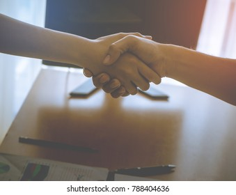 Woman and Man shaking hand over office table in bright orange light for team work success business concept