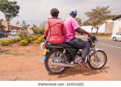 Woman and man sit back on motor bike on roadside. Kampala, Uganda.