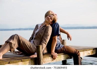woman and man sitting on pier at lake