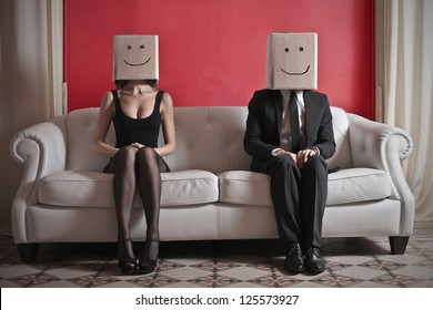 A woman and a man sitting on a sofa with a box on which is drawn a smile over their heads