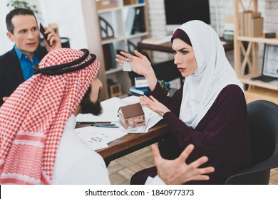 Woman and man slave sit and argue at the table. Male realtor speaks on the phone while an Arab family argues at a table about buying an apartment.