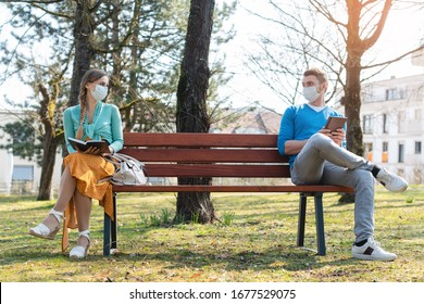 Woman and man in social distancing sitting on bench in park - Shutterstock ID 1677529075
