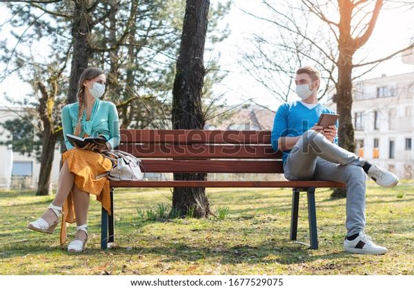 Femme et homme en distanciation sociale assis sur un banc dans un parc
