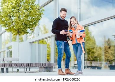 Frauen und Mann, die zusammen auf dem Universitätscampus studieren und sich gegenseitig Bücher ansehen