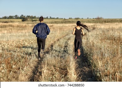 Woman and man training in field, jogging back view. Two young athletic people running in countryside on sunny day. Healthy lifestyle, sport, motivation, team concept. Photo with copy space