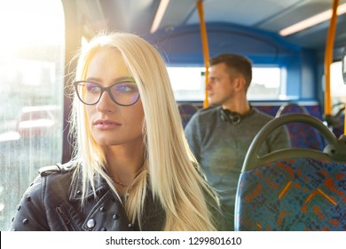 Woman and man travelling by bus in London. Beautiful blonde woman looking out of the window with sun comingh through, man on background. Lifestyle and travel concepts