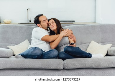 A woman and a man watch a movie on the couch