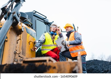 Woman and man worker in quarry on excavation machine looking into a bright future above the horizon