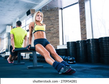Woman and man workout with hands on bench in gym