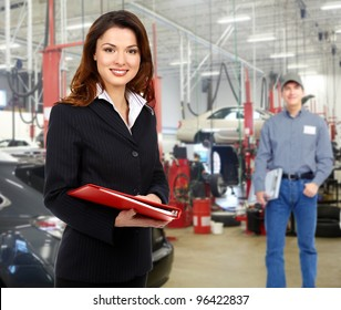 Woman manager in auto repair service. Garage.