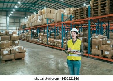 woman manager in large warehouse with digital tablet. young girl staff working in storehouse making inventory by touchpad. female worker in helmet and safety vest stock taking in stockroom.