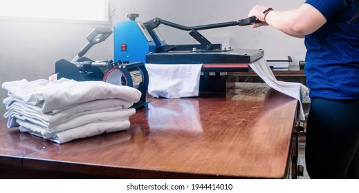 woman manipulating a sublimation machine ironing a shirt. advertising and screen printing concept.