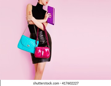 Woman with many colorful purses. Fashion addicted. Love for shopping. Isolated on pink background.