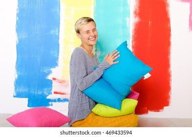 Woman with many pillows in hands. Indoor photo.