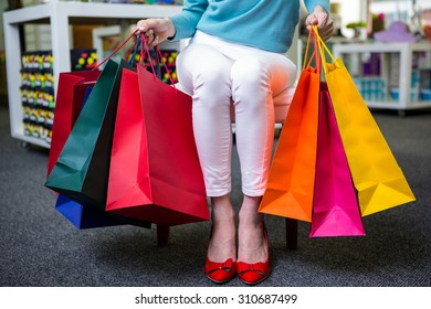 Woman with many shopping bags in fashion boutique