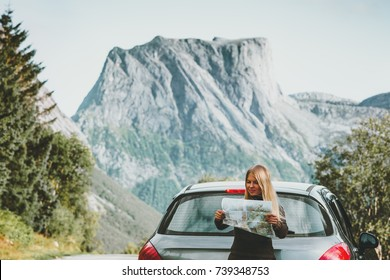 Woman with map on road trip planning journey route in Norway Travel Lifestyle concept adventure vacations outdoor mountains on background