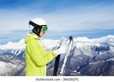 Woman with map of ski resort over mountains