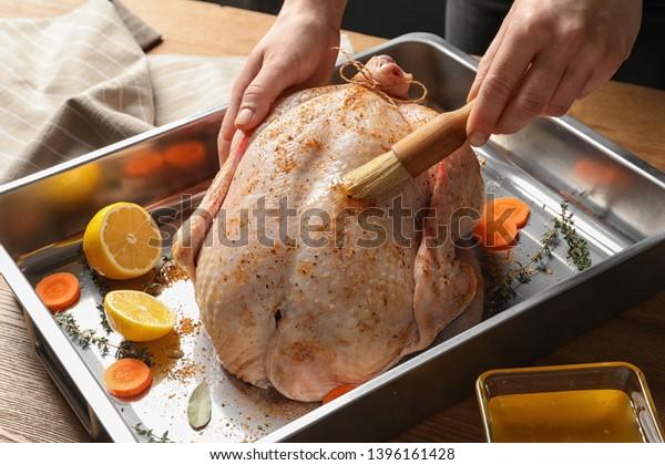 Woman marinating whole turkey at table, closeup