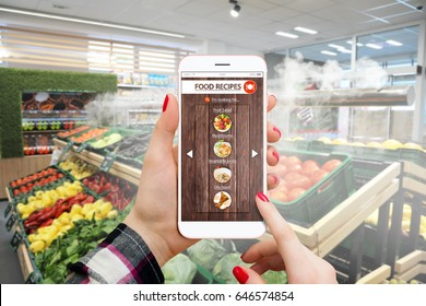 Woman in marketplace reading recepies on her smartphone and buying groceries