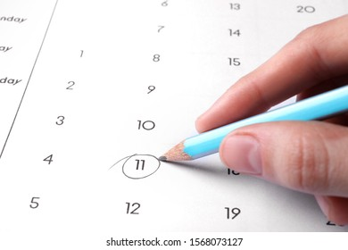 Woman marking date in calendar with pencil, closeup