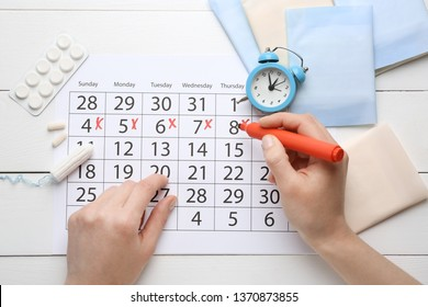 Woman marking her period in menstrual calendar