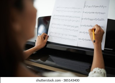Woman marking up in music sheet before playing