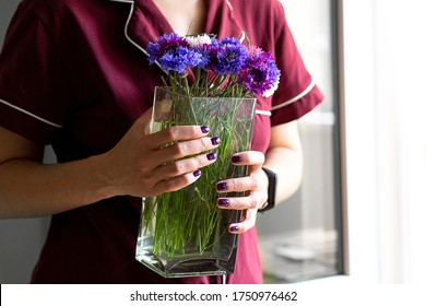 A woman in a maroon suit and purple fingernails holds a vase of cornflowers. Flower delivery service. Online order. Flower shop.