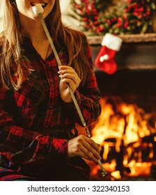 Woman with marshmallow by the fireplace. Young woman smiling and eating roasted marshmallow by the warm fireplace decorated for Christmas. Relaxed holiday evening concept.