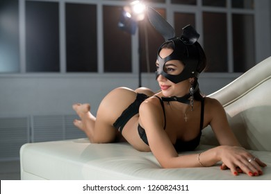 Woman in mask and bunny ears on the sofa shot
