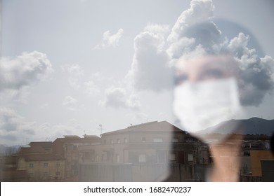 Woman with mask looking out the window through the glass to the outside, with the clouds reflected in the glass. During the confinement at home. Horizontal image. Concept covid-19.