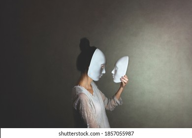 woman with mask looks at another mask of herself, concept of introspection