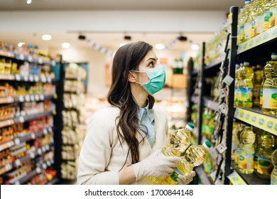 Woman with mask safely shopping for groceries amid the coronavirus pandemic in stocked grocery store.COVID-19 food buying in supermarket.Panic buying,stockpiling.Staples shortage.Cooking vegetable oil