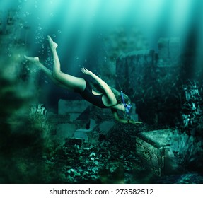 Woman with mask and snorkel diving swimming underwater among the ancient ruins to treasure chest. Focus on woman