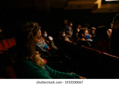 woman with mask watching a show in a theater keeping sanitary measures