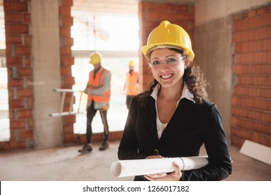 Woman with masons in new apartment building. Team of workers at work in house and portrait of happy female architect. Forewoman looking and smiling at camera
