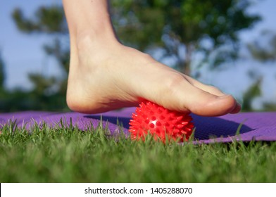 Woman massage feet with spiny plastic red massage ball in summer park. Self myofascial release concept, love your feet