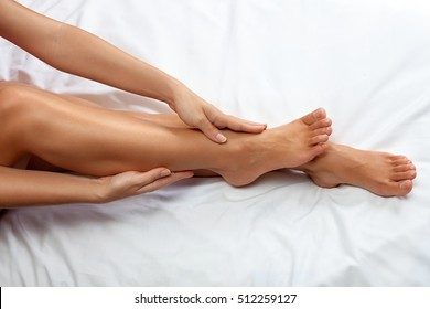 Woman massage her tired  legs and ankles