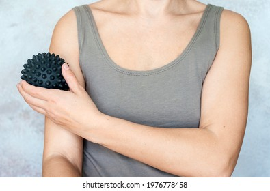 A woman massages her arm with spiky trigger point ball, muscle pain treatment reflexology. Physiotherapy concept