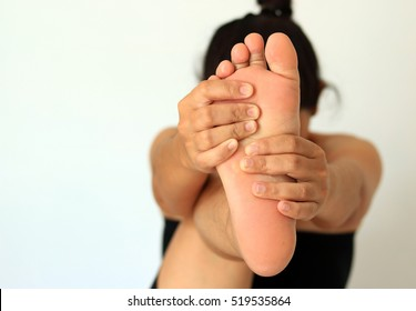 Woman massages her foot.  on a white background.