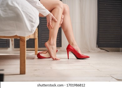 Woman massages tired legs in red stilettos