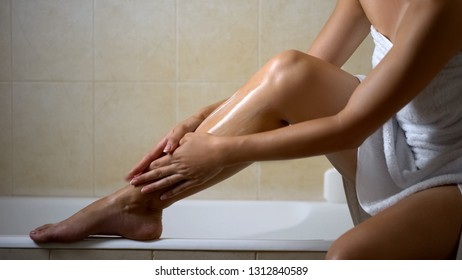 Woman massaging and creaming leg with lotion, hydration after depilation at home