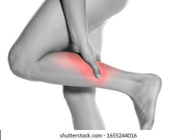 woman massaging her painful leg on white background