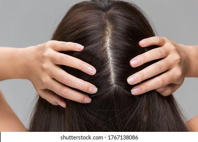 A woman is massaging her scalp.