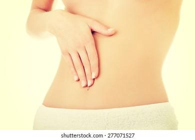 Woman massaging her slim belly.