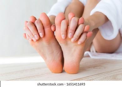 A woman massaging her sole.