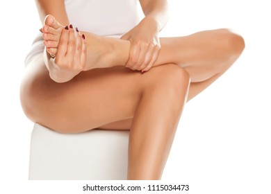 woman massaging her tired feet on white background