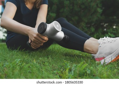 Woman massaging leg with massage percussion device after workout.