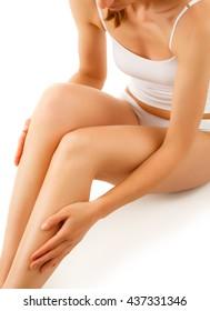 Woman massaging legs sitting on white background
