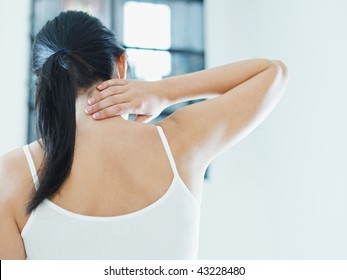 woman massaging neck. Rear view, copy space